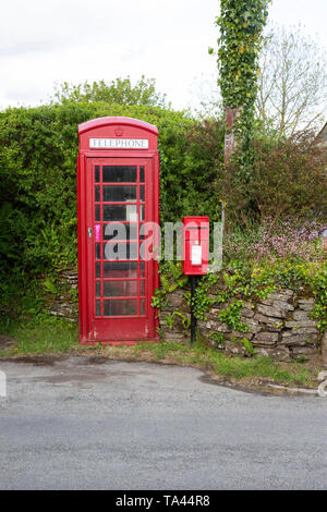 A traditional British red telephone box and Lamp box style postbox in a rural setting in Cornwall - Stock Photo