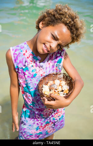 CAIRU, BRAZIL - FEBRUARY 2018: A young Brazilian girl sells souvenir shells from a small woven basket to visitors arriving on boat tours. - Stock Photo