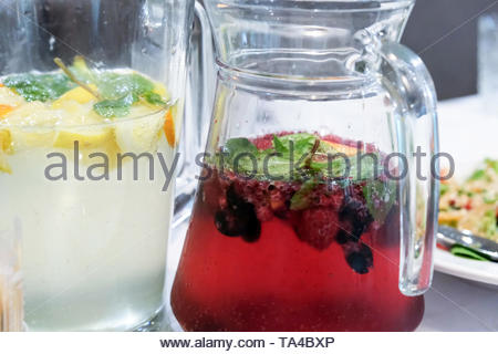 Glass jars with homemade citrus and berry drinks close up - Stock Photo