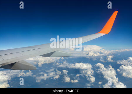 Wing of an airplane flying over white clouds in a blue sky - Stock Photo