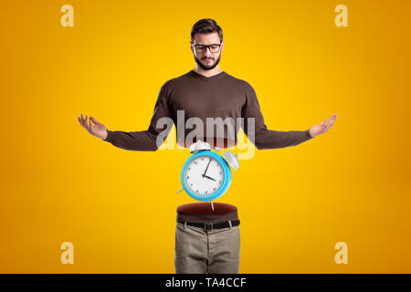 Young man in casual clothes cut in half with blue alarm clock inside on yellow background - Stock Photo