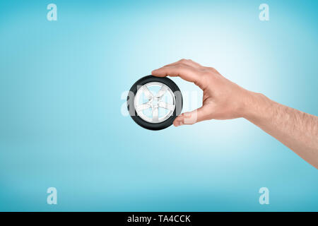 Male hand holding small car wheel tyre between fingers on blue background - Stock Photo