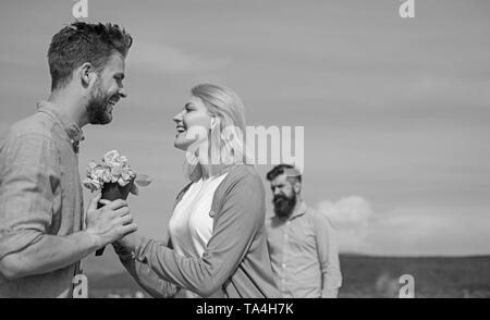 New love. Ex partner watching girl starts happy love relations. Couple in love dating outdoor sunny day, sky background. Couple with flowers bouquet romantic date. Ex husband jealous on background. - Stock Photo