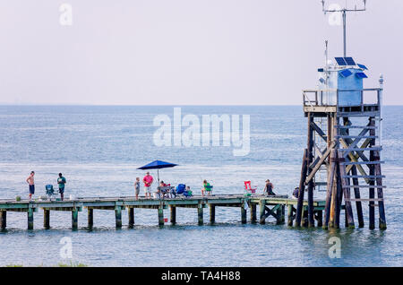 People fish on the public fishing pier beside a weather tower, Aug. 2, 2014, in Dauphin Island, Alabama. - Stock Photo