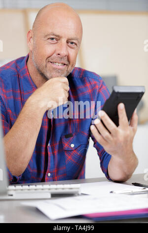 happy man calculating invoices using calculator in office - Stock Photo