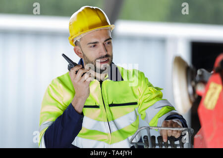 male engineer communicating on walkie-talkie at site - Stock Photo