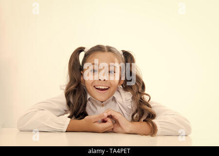 Excellent pupil lean on desk isolated white. Perfect schoolgirl with tidy fancy hair. School hairstyle ultimate top list. Prepare kid first school day. Schoolgirl happy smile cute ponytail hairstyle. - Stock Photo