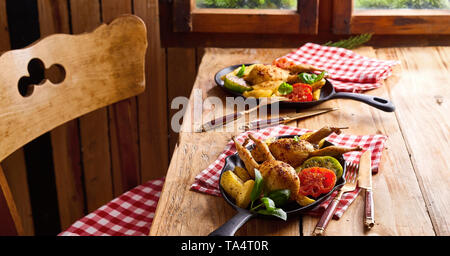 Serving of two crispy golden roast quails with roasted vegetables in a metal skillet at double place settings at a rustic table - Stock Photo