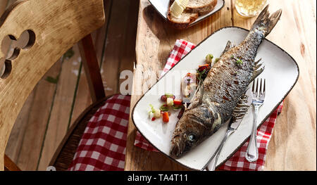 Whole grilled sea bass served on a platter garnished with vegetables on a rustic table in a tavern with bear and rye bread - Stock Photo