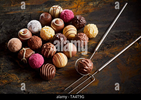 Handmade chocolate praline bonbon display with a neat rectangle of assorted fondants on rustic wood with wire lifter and fork - Stock Photo