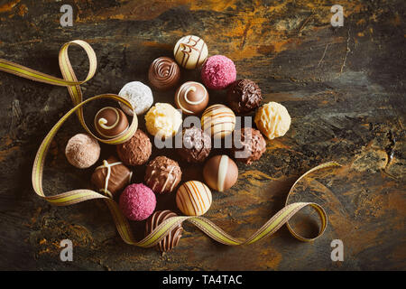 Elegant display of luxury chocolate pralines arranged in a neat rectangle with swirling gold ribbon on rustic wood viewed from overhead - Stock Photo