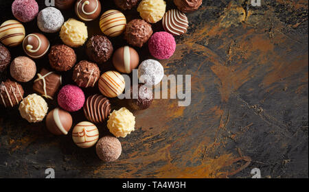 Flat lay display of luxury handmade chocolates arranged in neat rows on rustic wood with copy space viewed high angle - Stock Photo
