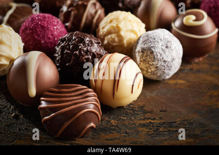 Luxury handmade decorative chocolate bonbon in a display of assorted pralines with selective focus in close up view on rustic wood - Stock Photo