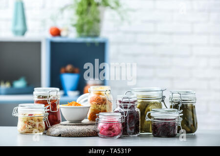 Assortment of tasty fermented vegetables on table in kitchen - Stock Photo