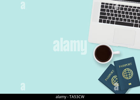 flat lay of two passport , coffee cup and computer laptop on pastel blue color background with copy space. travel , visa and vacation concept - Stock Photo