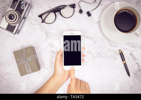 woman hand use mock up of mobile phone blank black screen with finger on touch screen with earphone,  pen, camera, glasses , cup of coffee and gift bo - Stock Photo