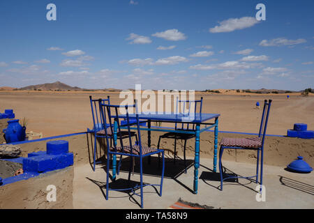 Blue table and chairs on a cafe terrace with a great view on the dunes near Merzouga, Morocco - Stock Photo