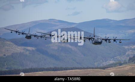 A rare group of four USAF C-130 Hercules aircraft fly at low level through LFA 7, Mach Loop near Dolgellau, Wales, UK. - Stock Photo