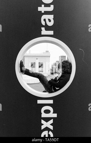 A boy with curly hair and jeans sitting inside the O opening of the Exploratorium sign in San Francisco, California. - Stock Photo