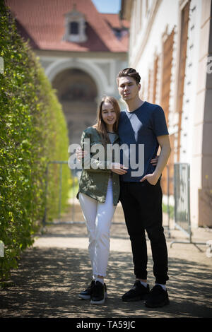 A young couple traveling. Standing on the street and hug. Mid shot - Stock Photo