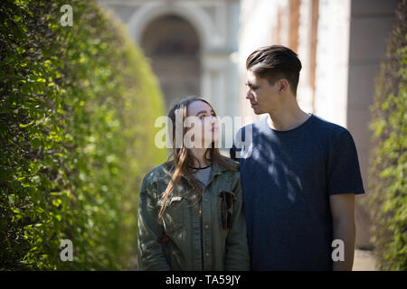 A young couple traveling. Standing on the street and looking at each other. Mid shot - Stock Photo