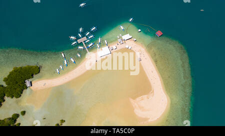 Island hopping Tour at Honda Bay, Palawan. An island of white sand with mangroves. Atoll with a white island, view from above. Boats and tourists on the Luli island