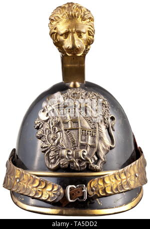 A helmet of the Savoy horseguard militia, circa 1850 Skull of black lacquered brass sheet. Gilt embossed comb, the front embellished with a large, elaborate lion head relief. Silver plated emblem with the large coat of arms of Savoy, one-piece embossed chinscales on smooth rosettes, left with original leather cockade, green underlined visors. Well preserved lining of tender brown leather (with loops). Signs of wear and age. Only slightly worn, in untouched original condition. historic, historical, Italian, Europe, European, 19th century, Additional-Rights-Clearance-Info-Not-Available - Stock Photo