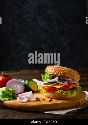 Sandwich burger with ham, cheese and vegetables on a wooden board with ingredients. Copy space. Fast food for breakfast or lunch. Concept for banner o - Stock Photo