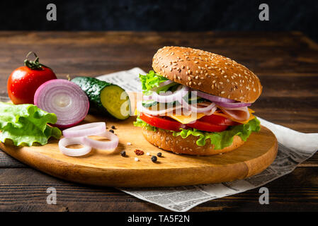 Sandwich burger with ham, cheese and vegetables on a wooden board with ingredients. Copy space - Stock Photo