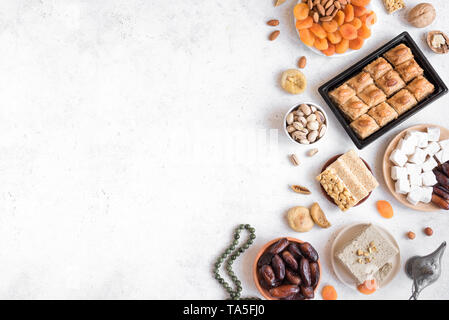 Assortment, set of Eastern, Arabic, Turkish sweets, nuts and dried fruits on white table, top view, copy space. Holiday Middle Eastern traditional swe - Stock Photo