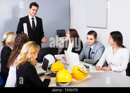 Team of engineers discussing business project and smiling in office - Stock Photo