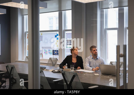 Two business people listening in a conference room - Stock Photo