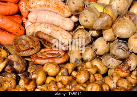 Grilled potatoes and sausages cooked outdoors on a bright sunny spring day - Stock Photo