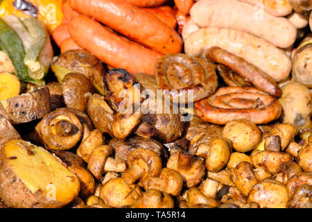 Grilled potatoes, mushrooms and sausages cooked outdoors on a bright sunny spring day - Stock Photo