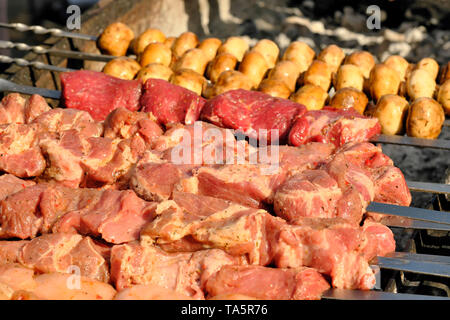 Grilled potatoes and meat cooked outdoors on a bright sunny spring day - Stock Photo