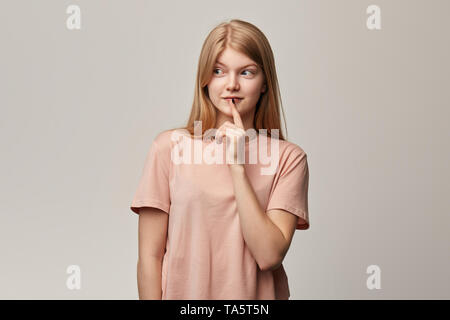 thoughts and idea concept. Attractive smiling cunning girl looks pensively, keeps on her lips, plans day, weekend, holiday, has something in mind, iso - Stock Photo