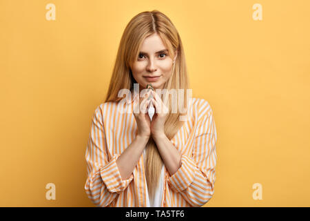 awesome good looking blonde woman with fingers in front of her face looking at the camera. close up photo. isolated yellow background. - Stock Photo