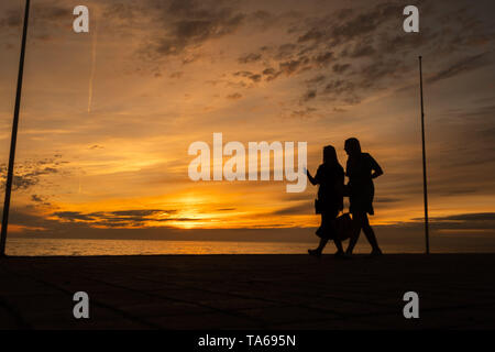 Aberystwyth Wales UK, Wednesday 22 May 2019  UK Weather: Two women  silhouetted  strolling along the seafront promenade at sunset in Aberystwyth on a mild May evening, at the end of a day of warm spring sunshine on the west coast of Wales. photo credit: Keith Morris / Alamy Live News - Stock Photo