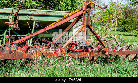 Old, rusty and abandoned agricultural machinery among the undergrowth on a fruit farm, kongskilde grower triland, sunny spring day in Oensel south Lim - Stock Photo