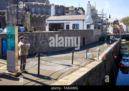 An older man about to take a photograph of Castletown harbour with Costa coffee and the castle in the background - Stock Photo