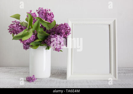 White photo frame and bouquet of purple lilac flowers in vase. Space for text. Vintage. Mother day mock up. - Stock Photo