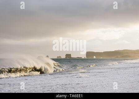 View of Cape Dyrholaey from Reynisfjara Beach, Iceland. Big waves on the ocean. Stormy weather with strong wind. Beautiful evening sunlight - Stock Photo