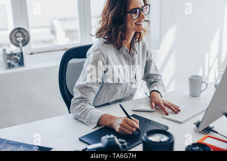 Young female photographer working on computer using drawing pad at office desk. Young caucasian woman using digital graphic tablet and drawing pen to  - Stock Photo
