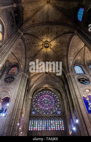A view of one of the famous Rose Windows inside Notre Dame de Paris with several other stained glass windows, columns, and ornate ceiling in the frame - Stock Photo