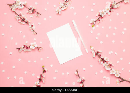 Invitation mockup of business paper A5 Flyer on a pink background with sprigs of spring sakura flowers. Empty space. Styled stock photo, web banner. F - Stock Photo