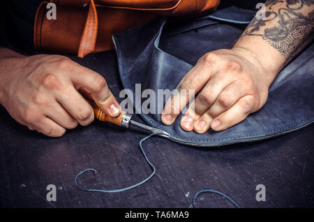 Currier of leather creates quality product of leather at his tanning shop - Stock Photo