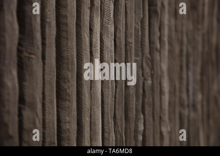 Pattern of vertical lines of  grey coloured wooden stakes, closely together, of a  picket fence in an acute angle in front of a small town garden. - Stock Photo