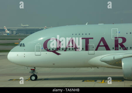 Airplane of Qatar Airways passing slowly on the runway of Heathrow Airport on its way to its gate for boarding passengers and its next flight to Doha. - Stock Photo