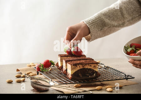 Female confectioner decorating tasty cakes at table - Stock Photo
