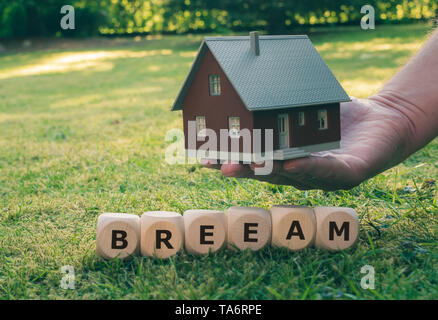 Cubes form the abbreviation BREEAM (Building Research Establishment Environmental Assessment Method) in front of a model house. - Stock Photo
